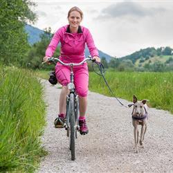 Frau mit Hund beim Radfahren in Oberammergau